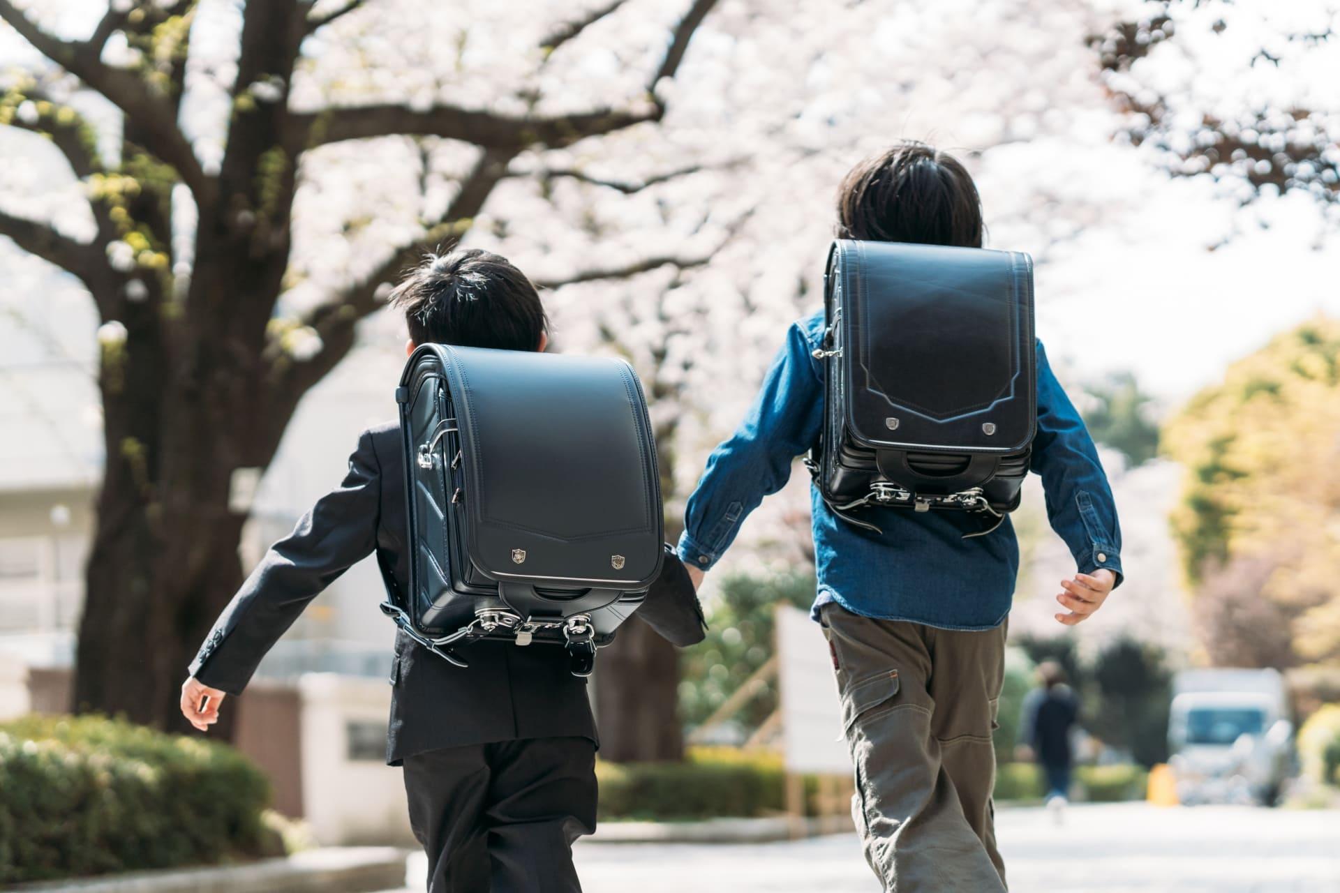 桜の木の下で手をつないで登校する兄弟