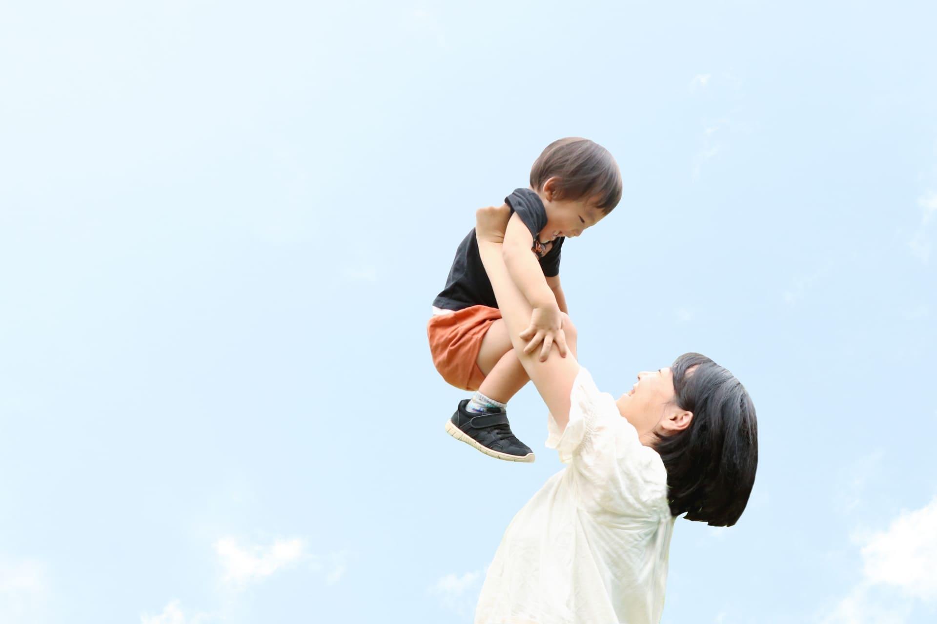 空の下で子供抱き上げるお母さん
