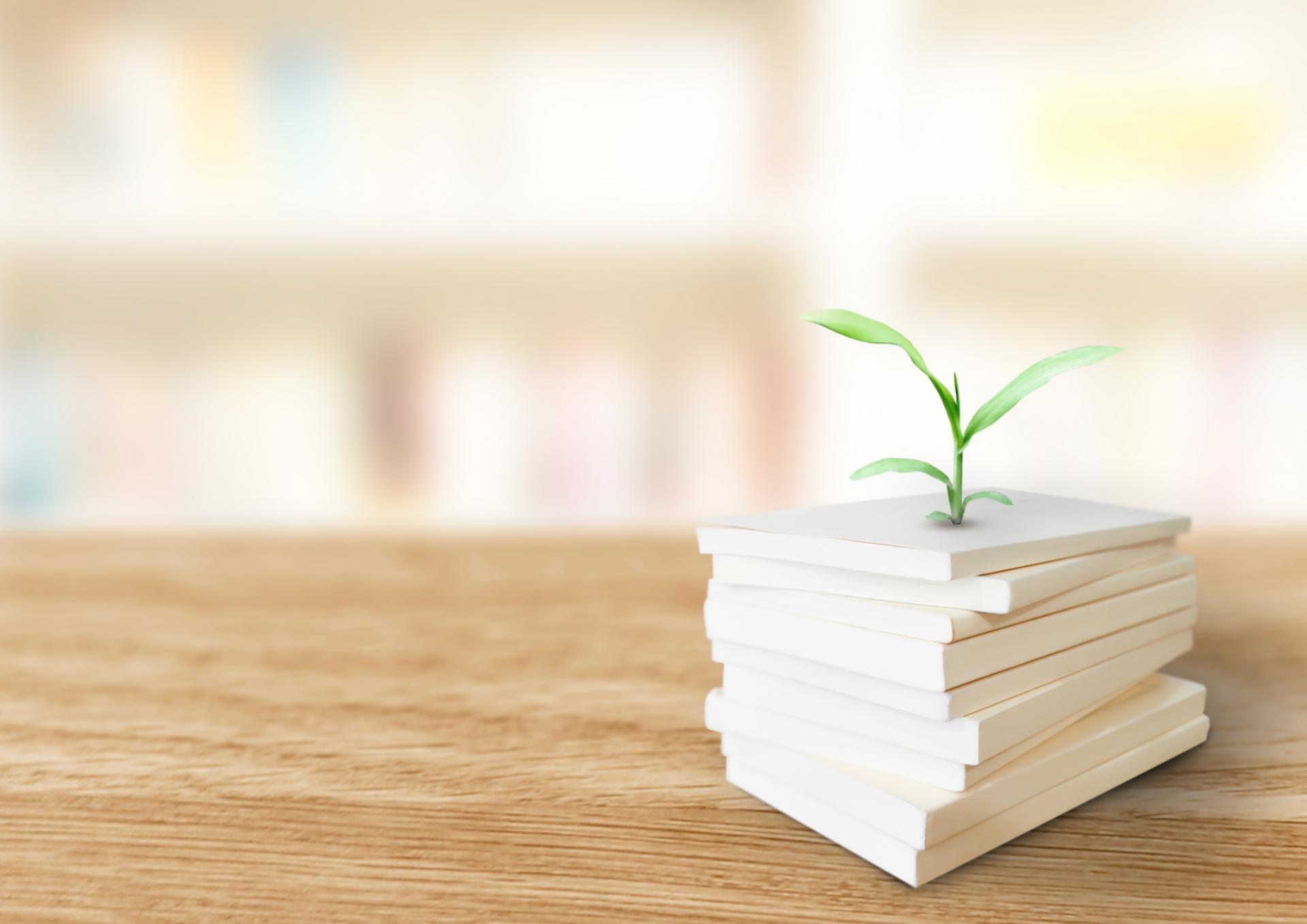 積み重なった本から緑が芽生える
