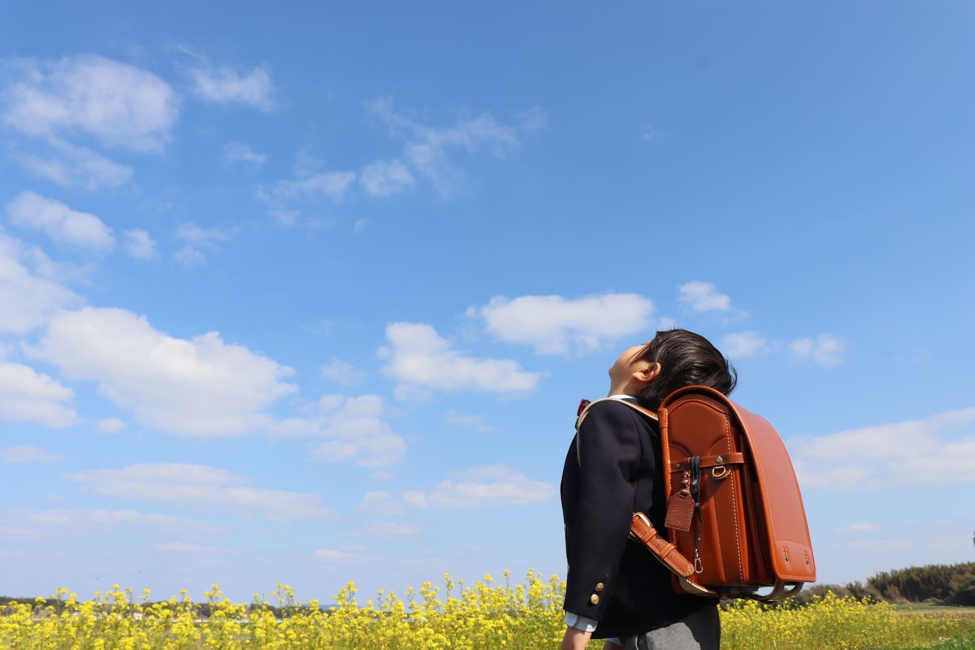 青空を見上げる小学生の女の子