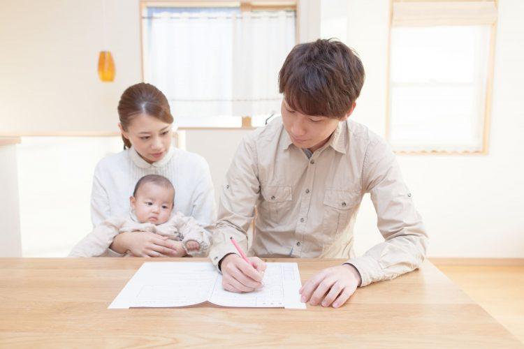 赤ちゃんを抱く女性の隣で男性が婚姻届けを記入