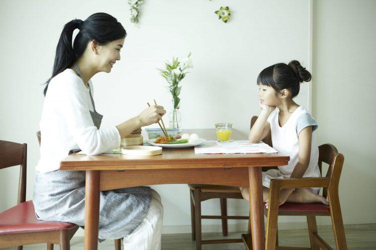 食卓を挟む女の子とママ