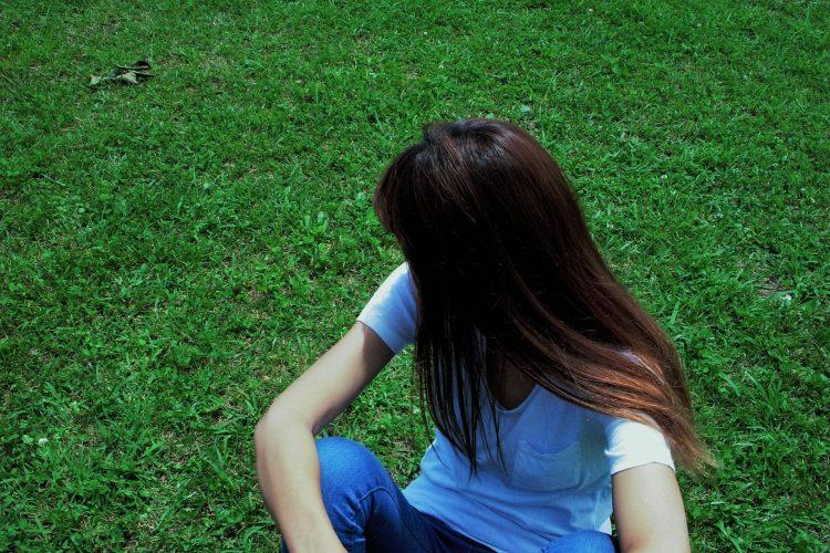 芝生に座って顔を背ける女性