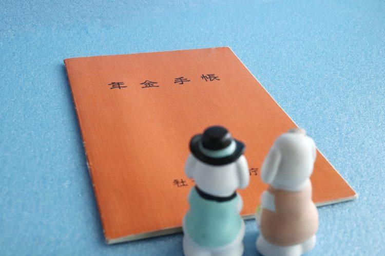 年金手帳を見つめる夫婦の人形