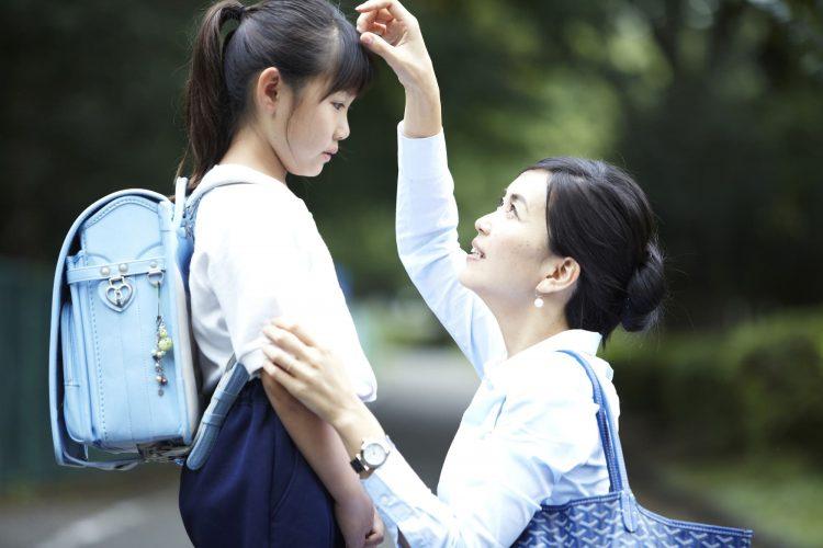 小学生の女の子の面倒をみるシングルマザー